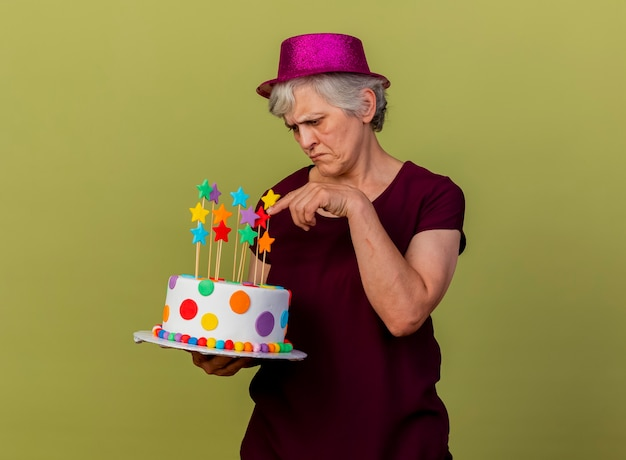 Unpleased elderly woman wearing party hat holds and points at birthday cake isolated on olive green wall with copy space