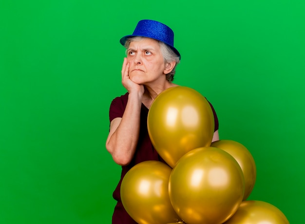Donna anziana dispiaciuta che indossa il cappello da festa mette la mano sul mento in piedi con palloncini di elio e guardando il lato sul verde