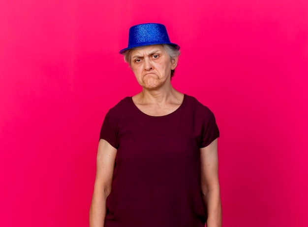 ピンクの上にパーティーハットをかぶった不機嫌な年配の女性