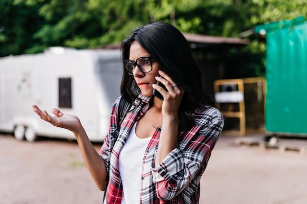 朝の電話で話している流行のメガネで不機嫌なエレガントな女性。路上で悲しそうな表情でポーズをとる魅力的な女の子の屋外ショット。