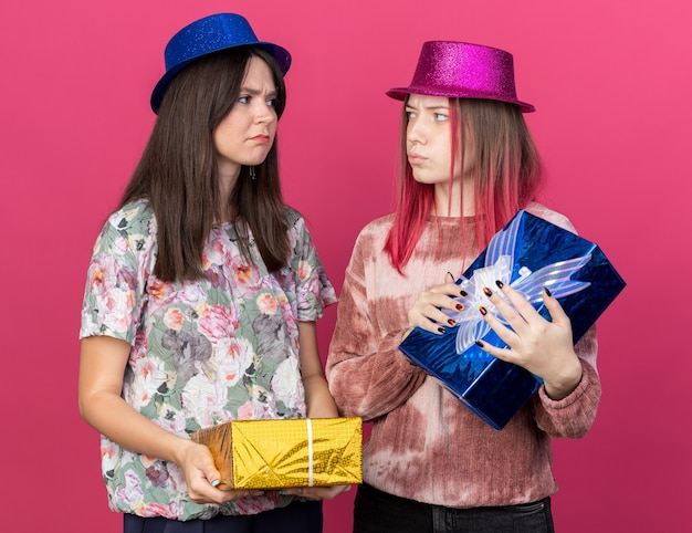 Unpleased girls wearing party hat holding gift boxes look at each other isolated on pink wall