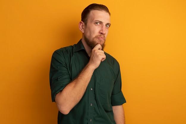 L'uomo biondo bello dispiaciuto tiene il mento isolato sulla parete arancione