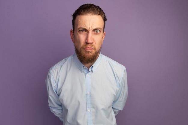 보라색 벽에 고립 된 앞을보고 불쾌 하 게 잘 생긴 금발 남자