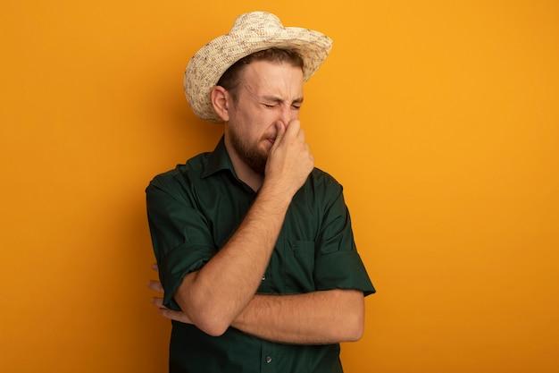 Uomo biondo bello dispiaciuto con cappello da spiaggia chiude il naso isolato sulla parete arancione