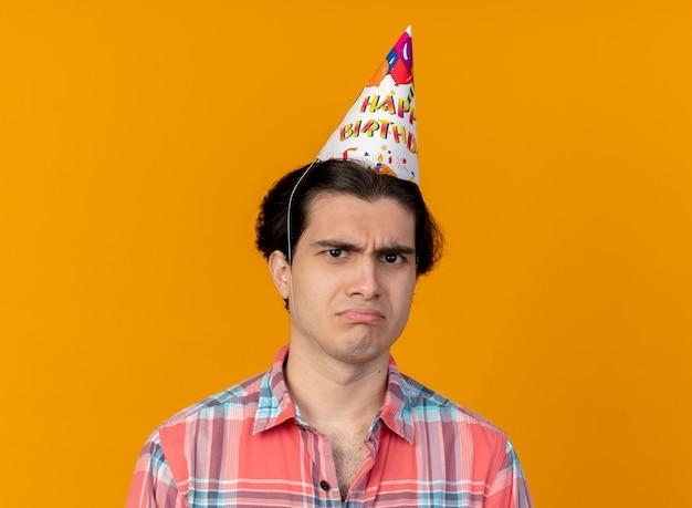 Unpleased handsome caucasian man wearing birthday cap looks at camera