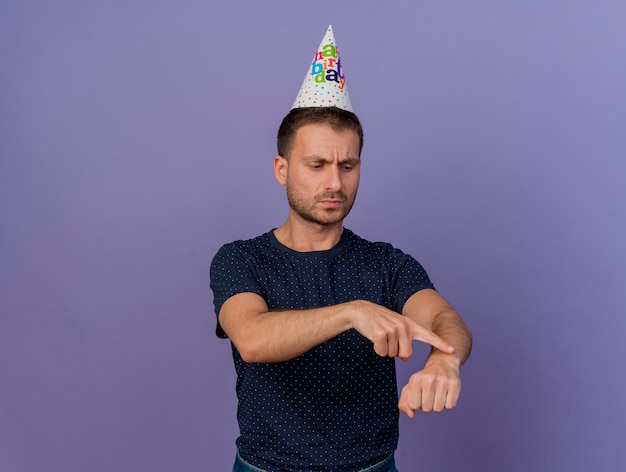 Uomo caucasico bello dispiaciuto che indossa il berretto di compleanno sembra e punti a portata di mano isolati su sfondo viola con spazio di copia