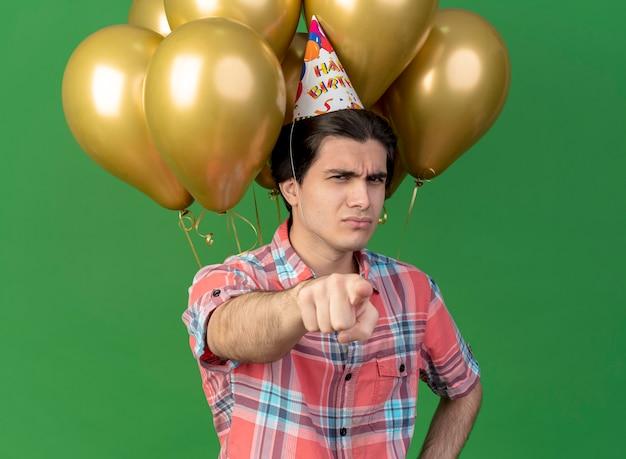 誕生日の帽子をかぶった不愉快なハンサムな白人男性が、カメラを指すヘリウム風船の前に立つ