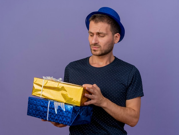 Unpleased handsome caucasian man wearing blue hat holds and looks at gift boxes isolated on purple background with copy space