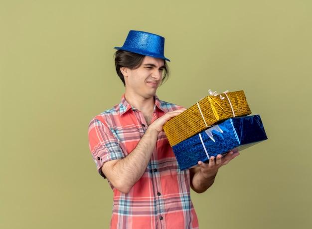 파란색 파티 모자를 쓰고 불쾌한 잘 생긴 백인 남자가 선물 상자를 보유하고 있습니다.
