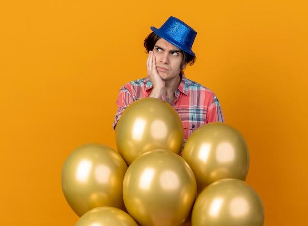 Uomo caucasico bello dispiaciuto che indossa il cappello blu del partito mette la mano sul viso e sta