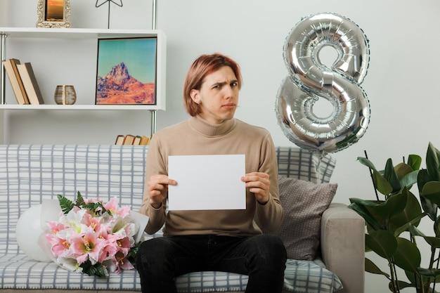 リビングルームのソファに座ってまばたきを保持している幸せな女性の日に不機嫌なハンサムな男
