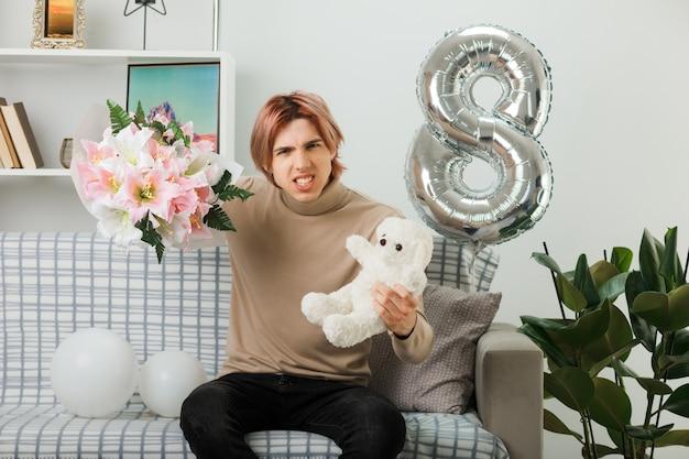 リビングルームのソファに座っているテディベアと花束を保持している幸せな女性の日に不機嫌なハンサムな男