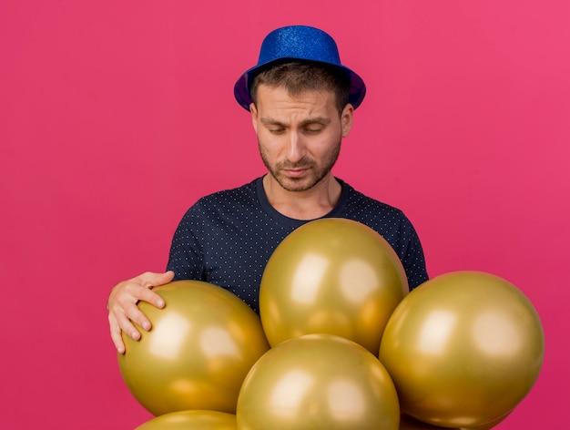Недовольный красавец в синей шляпе держит гелиевые шары, изолированные на розовой стене с копией пространства