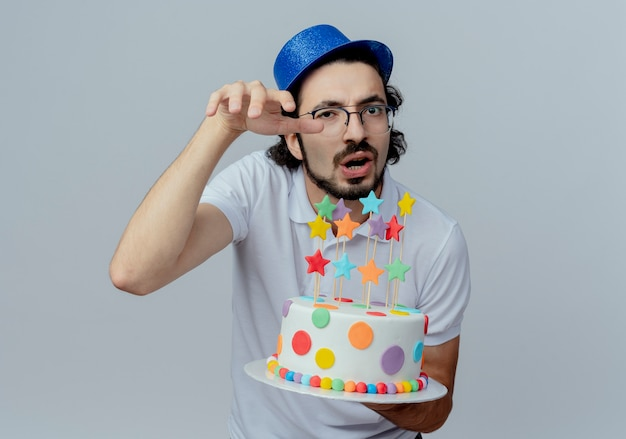 白で隔離のケーキを保持している眼鏡と青い帽子を身に着けている不機嫌なハンサムな男