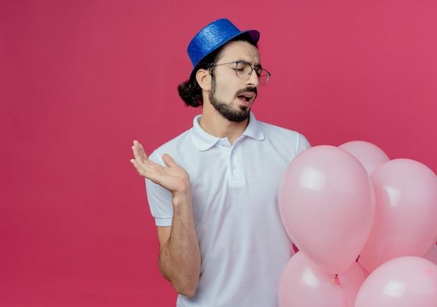 Uomo bello dispiaciuto che indossa occhiali e cappello blu tenendo e guardando palloncini e diffondere la mano isolata sul rosa