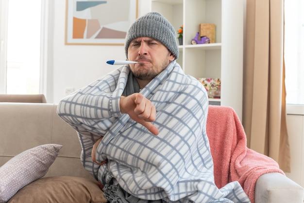 Scontento uomo malato con sciarpa intorno al collo indossando cappello invernale avvolto in plaid misurando la sua temperatura con termometro e pollice verso il basso seduto sul divano in soggiorno