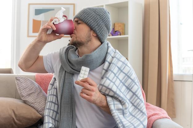 Недовольный больной славянский мужчина с шарфом на шее в зимней шапке, завернутой в плед, держит блистерную упаковку с лекарствами и пьет из чашки, сидя на диване в гостиной