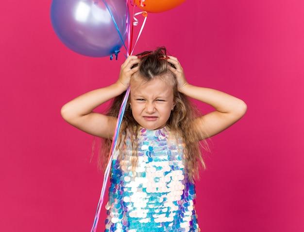 Scontenta bimba bionda che mette le mani sulla testa tenendo palloncini di elio isolati sulla parete rosa con spazio copia