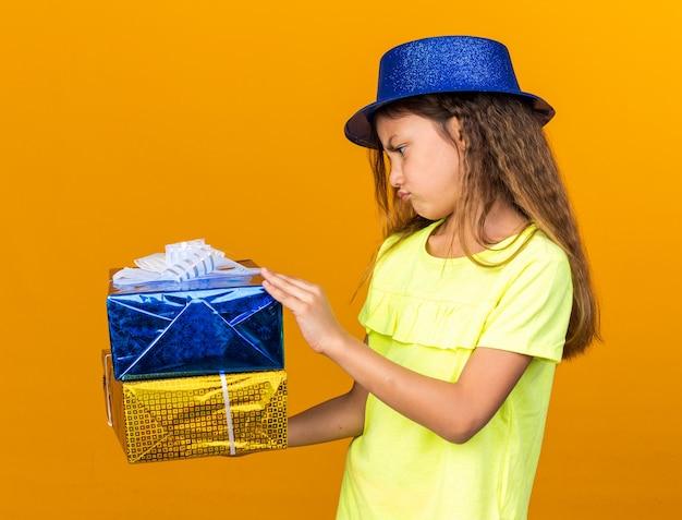 Piccola ragazza caucasica scontenta con cappello da festa blu che tiene in mano e guarda scatole regalo isolate sulla parete arancione con spazio copia