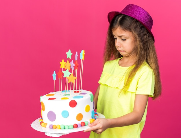 コピースペースでピンクの壁に分離されたバースデーケーキを保持し、見て紫色のパーティハットを持つ不機嫌な白人少女