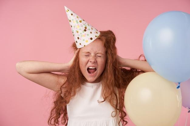 手のひらで耳を覆い、目を閉じ、かんしゃくを投げ、大きく開いた口で叫び、誕生日の帽子のピンクのスタジオの背景の上に立っている長いセクシーな髪の不機嫌な小さな巻き毛の女の子
