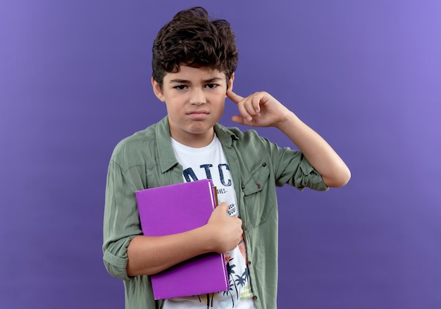 Unpleased little schoolboy holding books and putting finger on ear isolated on purple wall