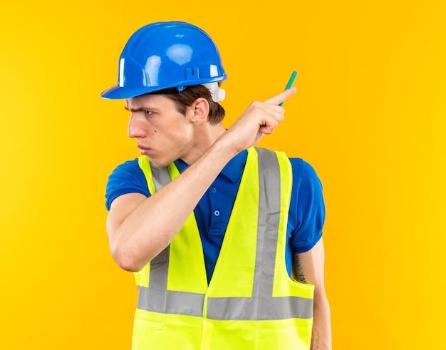 鉛筆と後ろを指す制服を着た若いビルダーの男性を見て不満