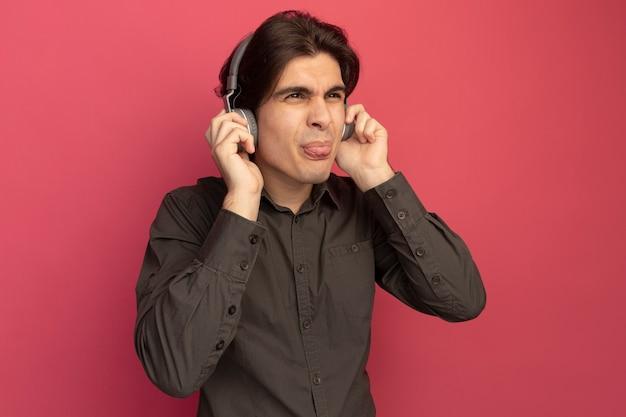 ピンクの壁に分離された舌を示すヘッドフォンと黒のtシャツを着ている若いハンサムな男を見て不満