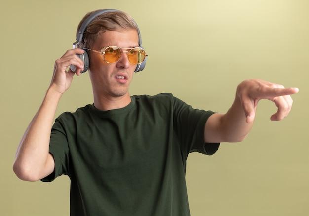 オリーブグリーンの壁に隔離された側に眼鏡とヘッドフォンポイントと緑のシャツを着ている側の若いハンサムな男を見て不満
