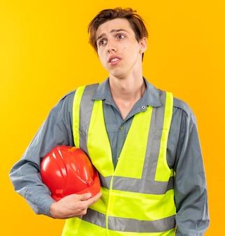Guardare scontento il giovane costruttore in uniforme che tiene il casco di sicurezza