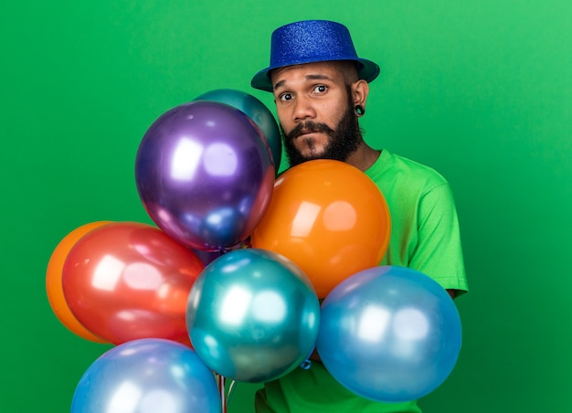 気球を持ってパーティーハットをかぶっている不機嫌そうなカメラの若いアフリカ系アメリカ人の男