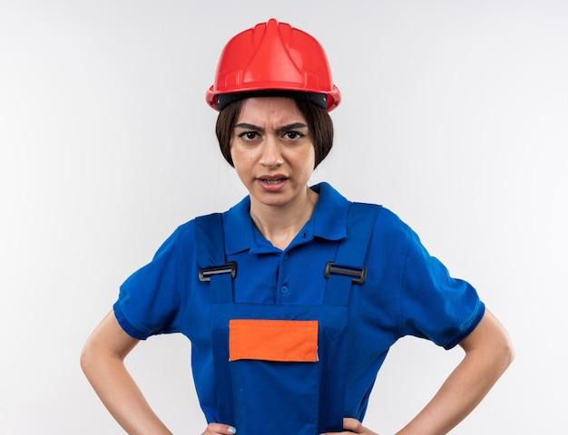 Dispiaciuto guardando la telecamera giovane donna del costruttore in uniforme che si tiene per mano sull'anca
