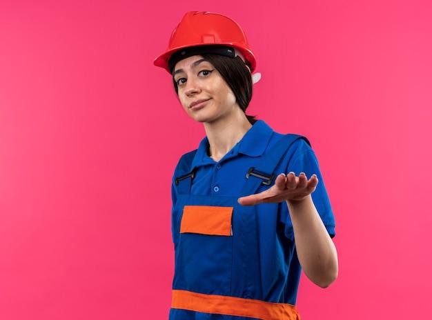Scontento guardando la telecamera giovane donna del costruttore in uniforme che tende le mani alla telecamera