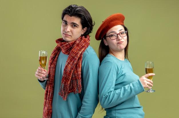 バレンタインデーの男がオリーブグリーンの背景に分離されたシャンパンのガラスを保持している帽子をかぶってスカーフの女の子を着て不機嫌そうなカメラの若いカップル