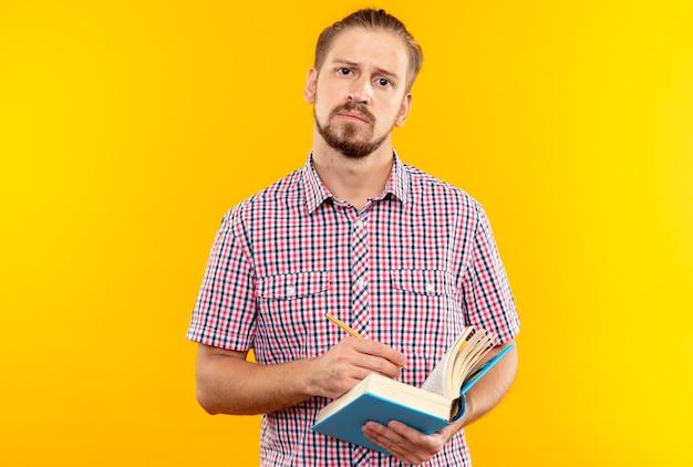 Giovane studente con fotocamera dall'aspetto scontento che indossa uno zaino con in mano un libro isolato su una parete arancione