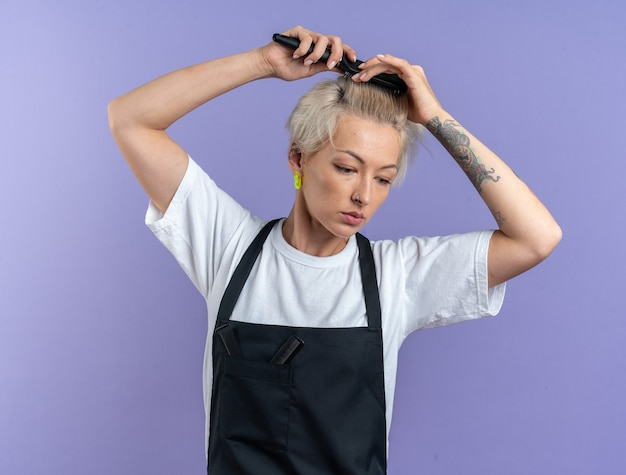 Unpleased looking down young beautiful female barber in uniform combing hair isolated on blue background