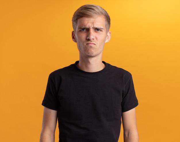 Scontento guardando davanti giovane bel ragazzo che indossa la camicia nera isolata sul muro giallo