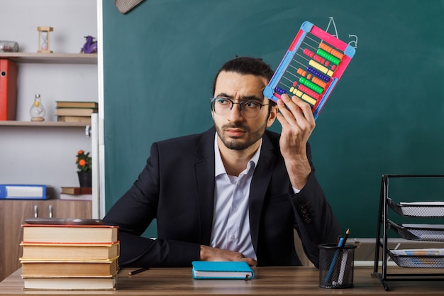 Unpleased looking side male teacher wearing glasses holding abacus sitting at table with school tools in classroom