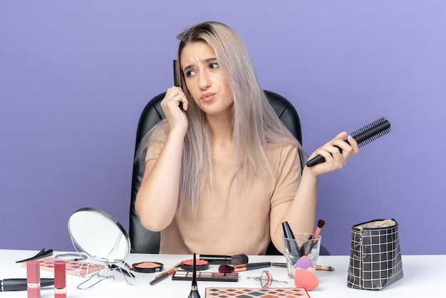 不機嫌そうな側面の若い美しい少女は、青い背景で隔離の髪をとかす化粧ツールでテーブルに座っています
