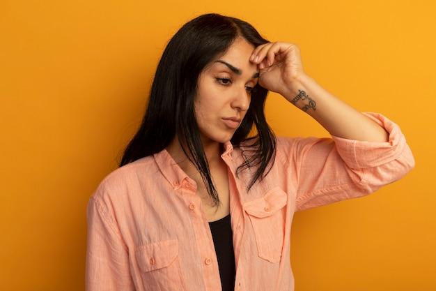 Scontento guardando lato giovane bella ragazza che indossa la maglietta rosa mettendo la mano sulla fronte isolata sul muro giallo