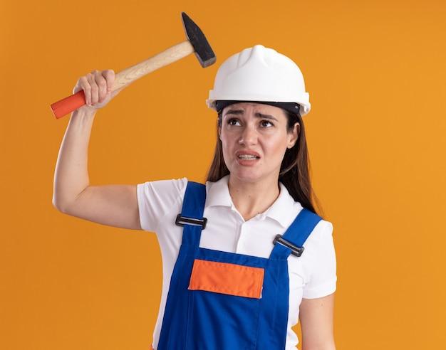Soddisfatto guardando lato giovane costruttore donna in uniforme tenendo un martello isolato sulla parete arancione