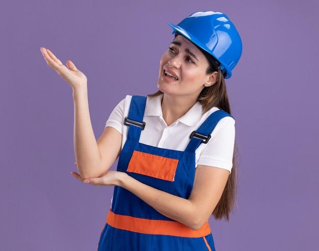 Soddisfatto guardando lato giovane costruttore donna in punti uniformi con la mano a lato isolato sulla parete viola
