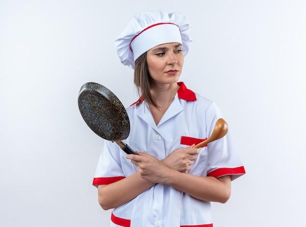 Scontento guardando lato giovane cuoca che indossa l'uniforme dello chef tenendo e attraversando la padella con il cucchiaio isolato sul muro bianco