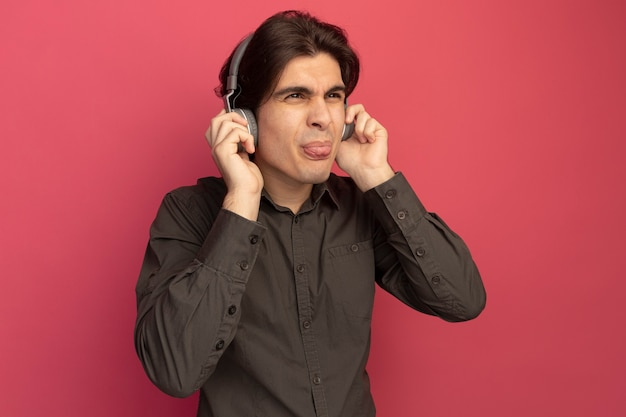 Unpleased looking at side young handsome guy wearing black t-shirt with headphones showing tongue isolated on pink wall