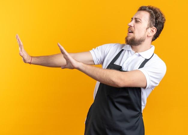 黄色の背景で隔離の側で手を差し伸べる制服を着ている不機嫌そうな側面の若い男性の理髪師