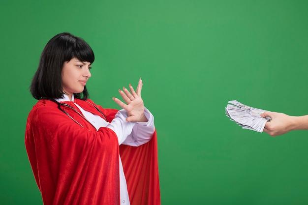 Scontento guardando lato giovane ragazza del supereroe che mostra il gesto di non indossare lo stetoscopio con veste medica e mantello qualcuno che le dà soldi isolato sul muro verde