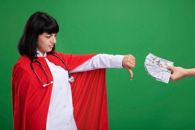 Scontento guardando al lato giovane ragazza del supereroe che mostra il pollice verso il basso indossando uno stetoscopio con veste medica e mantello qualcuno che le dà soldi