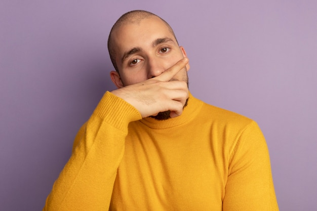 Unpleased looking straight ahead young handsome guy wiping nose with hand isolated on purple