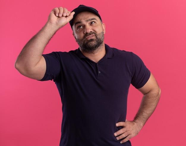 Недовольно смотрит вверх курьер среднего возраста в униформе и кепке, положив руку на бедро и держа кепку, изолированную на розовой стене
