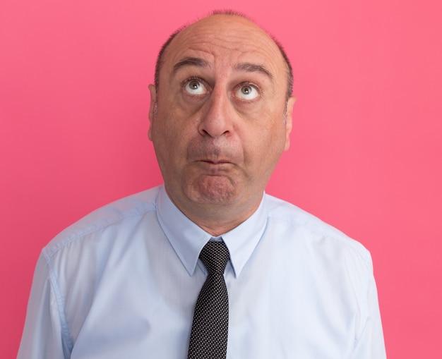 Недовольный мужчина средних лет в белой футболке с галстуком изолирован на розовой стене
